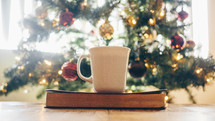 coffee mug on a Bible in front of a Christmas tree