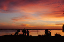Silhouettes of people on the beach looking at a colorful sunset.