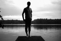 Silhouette of a man standing on a pier on a lake.