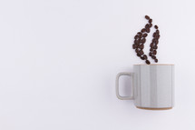 coffee beans in the shape of steam from a mug on a white background
