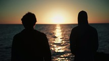 friends standing on a shore looking out over the ocean at sunset