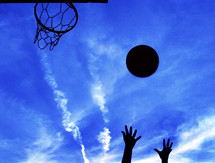 Silhouette of hands throwing basketball towards hoop with bliue sky in the background.
