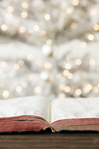 worn open Bible on a wood floor in front of a Christmas tree