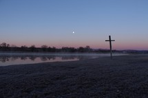 cross by a pond under a pink sky