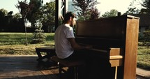 man playing a piano outdoor s