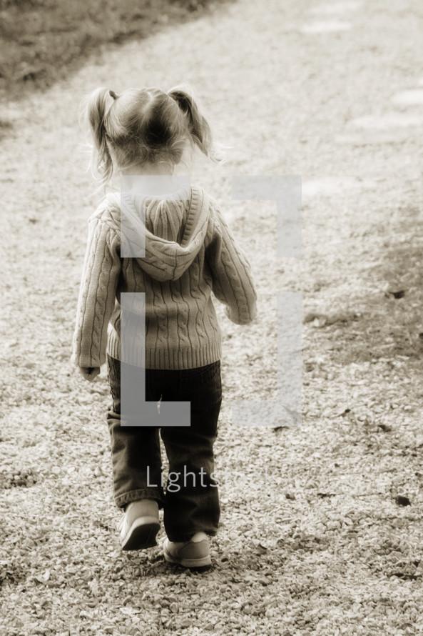 toddler girl in pig tails walking