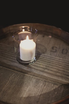 A candle on a wooden barrel