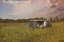 family sitting in an old van in a field