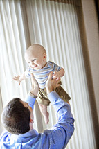 man holding up infant boy over his head - window