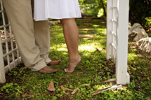 Barefoot woman on tip-toes standing to man with shoes