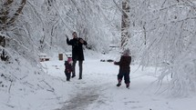father playing in the snow with his children