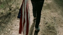 a man walking carrying an American flag