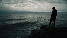 man standing on a rock on a shore looking out over the ocean