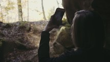 a woman filming a fall forest with her iPhone