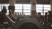 women using rowing machines in a gym
