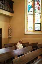 priest praying in a chapel