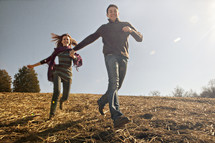 Couple running in field