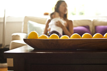 bowl of fruit on table - mother holding baby in background