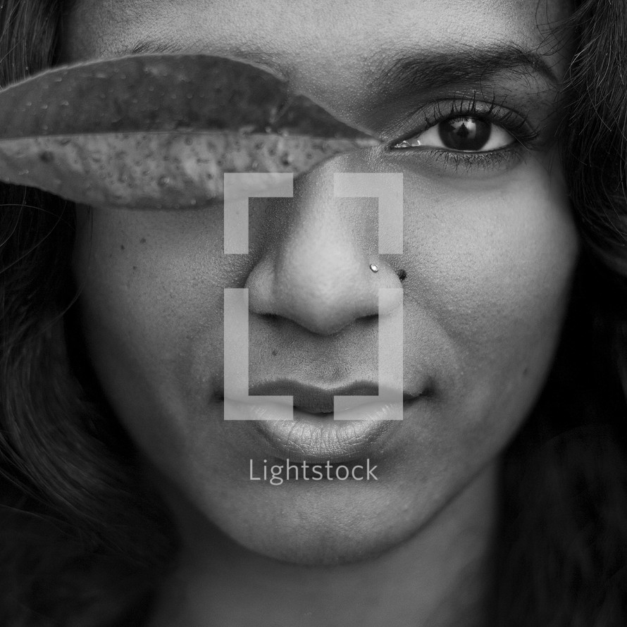 Woman holding a leaf in front of her eye.