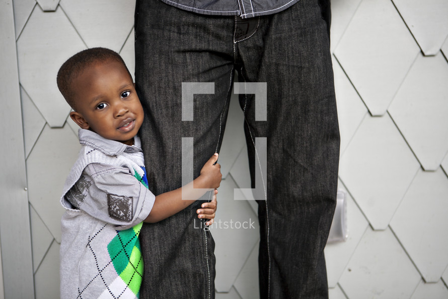 Boy holding onto father's leg