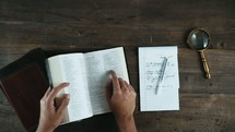 a person reading from a Bible taking notes and leaving