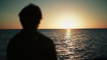 silhouette of a man standing on a shore looking out over the ocean at sunset