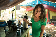 Homeless woman making coffee in a tent.