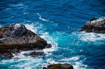 birds in flight over a rocks in the ocean