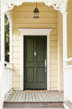A wooden porch leading to a green front door.