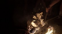 pulling a log from a fire