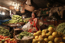 woman in India sitting with her hands together in a vegetable market