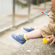 feet of a child in sneakers playing outdoors