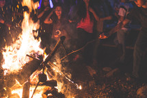 adding sticks to a bon fire
