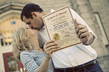 Newly married couple holding marriage certificate and kissing