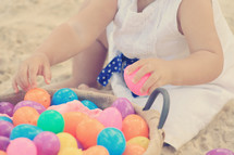 Child's hands holding Easter eggs in a basket.