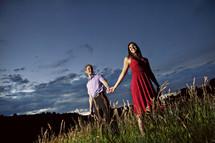 couple standing on hillside holding hands