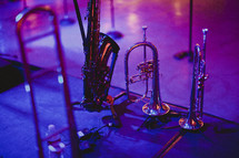 A saxophone, trumpet and horns sitting on a stage