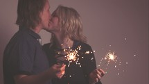 a couple holding sparklers and kissing
