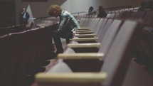 man with head bowed sitting in an auditorium
