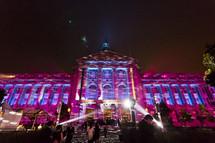 A large building lit by spotlights celebration party event lighting