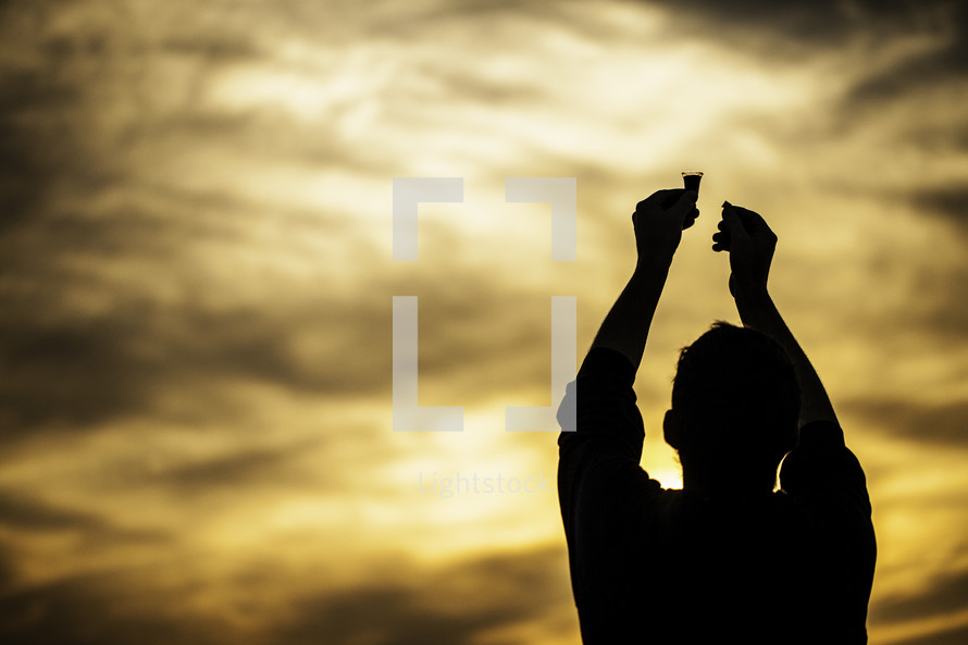 silhouette of a man holding up communion bread and wine to the sky in worship and praise to the Lord