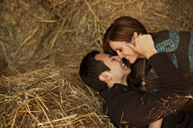 a couple kissing in hay