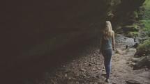 woman walking near a cave under a cliff