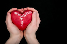 Hands holding a red ceramic heart.