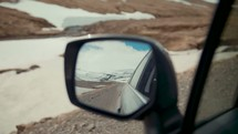 view of snow on mountains in a rearview mirror