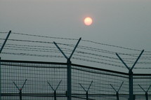 sun over a barbed wire lined fence