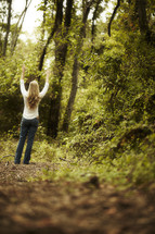 A woman with hands raised in a forest