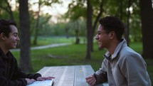 men sitting at a picnic table reading a Bible and discussing scripture