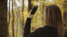 a woman taking pictures and filming a fall forest with her cellphone