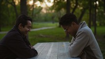 men sitting at a picnic table discussing scripture